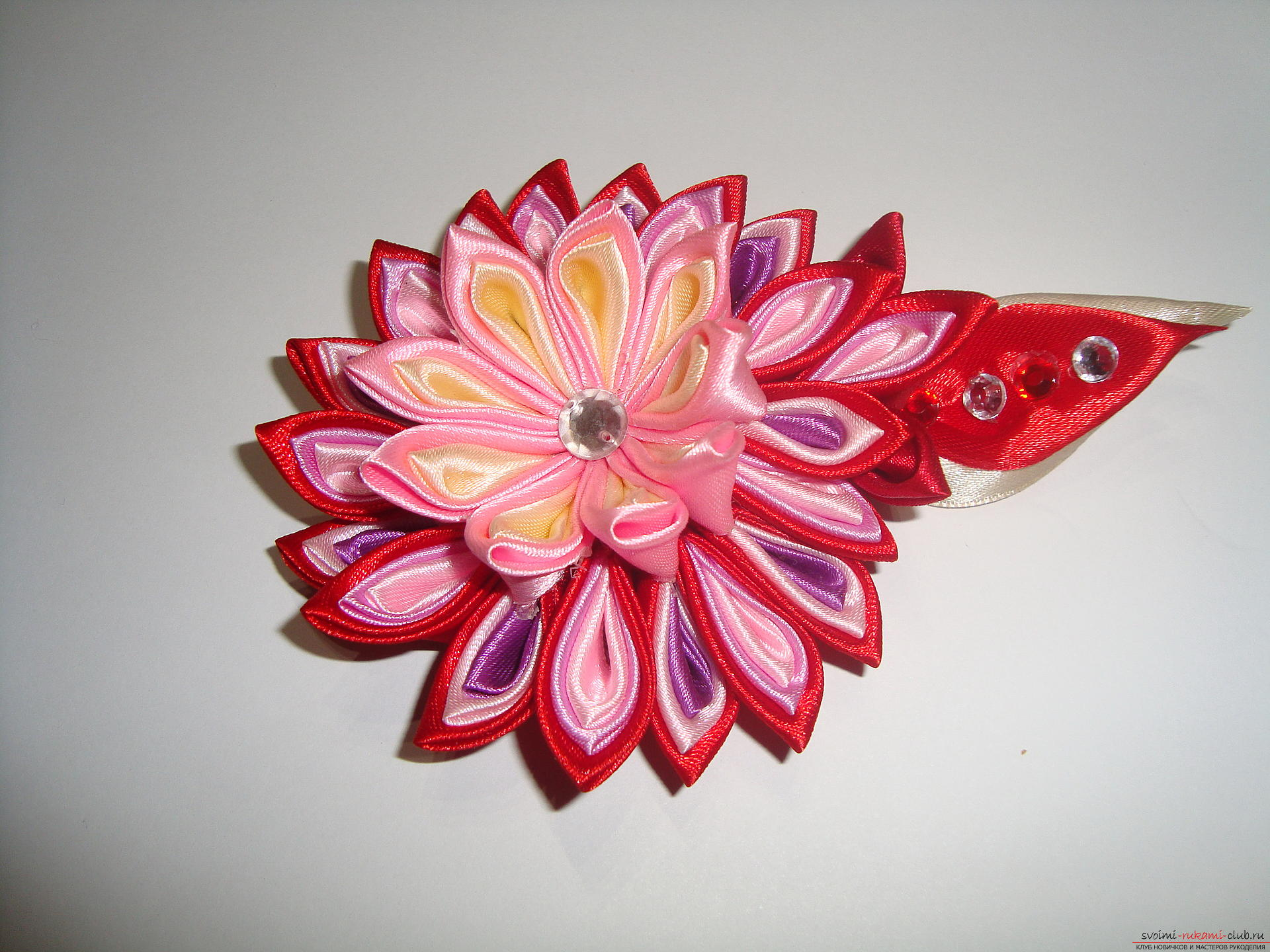A detailed guide with a photo on making a hairpin in the shape of a flower with multi-colored petals in Kansas technique. Photo №1