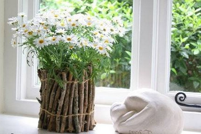 A flower pot decorated with wooden sticks