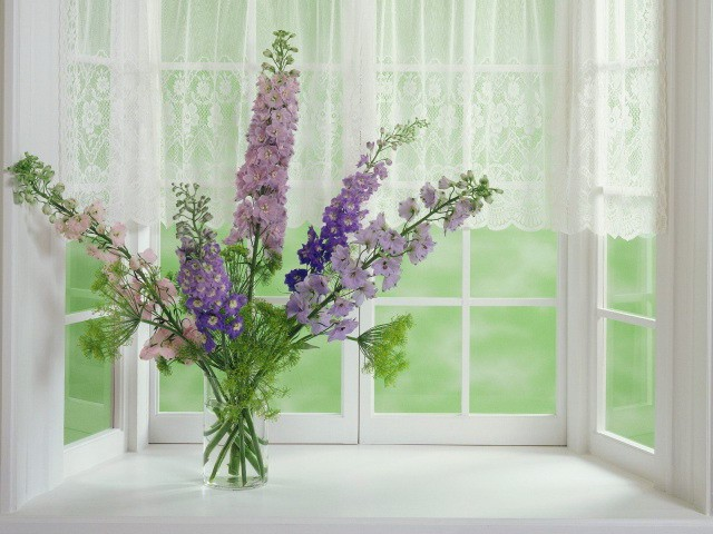 Vase of flowers: a bright accent on a white windowsill