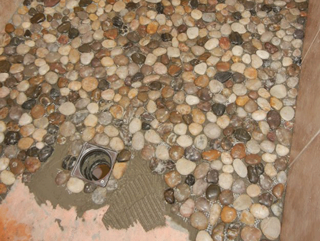The idea of ​​a floor for a shower niche made of stones
