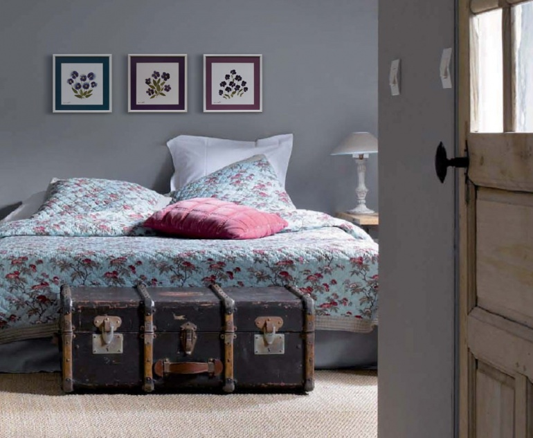 An old suitcase and herbariums in the bedroom interior remind of a pleasant journey