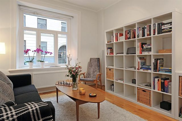 Bright Scandinavian interior of the living room with shelves