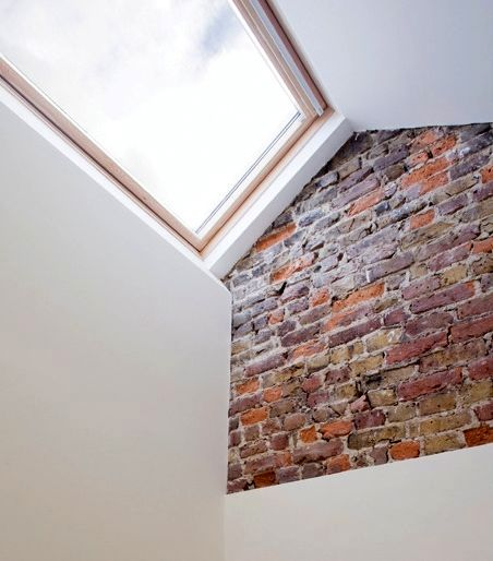 fragment of a brick wall in the interior of a narrow house